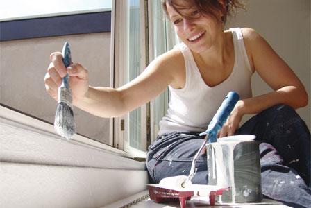 Woman painting window sill