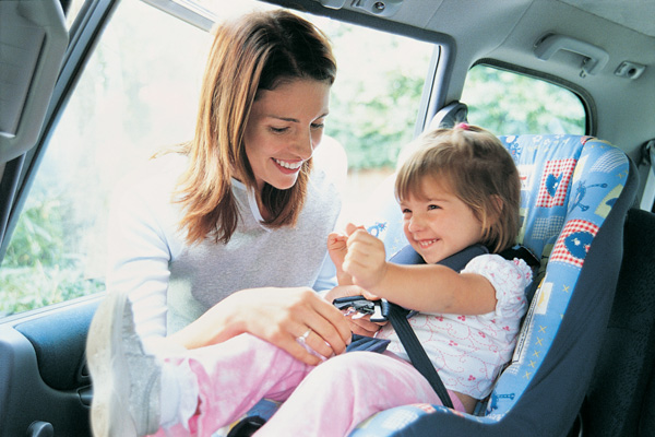 Woman putting child in carseat