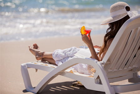 Woman reading book on beach while drinking cocktail