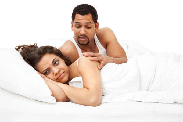 Woman rolling eyes at husband in bed