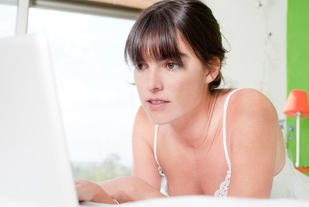 Woman using computer on her bed