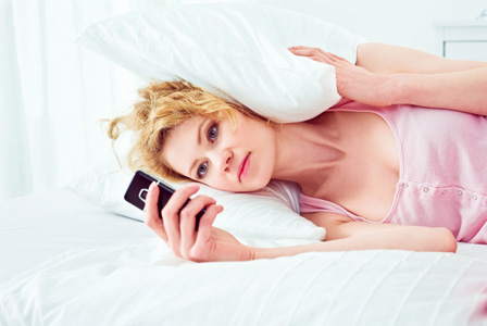 Woman waiting on text in bed