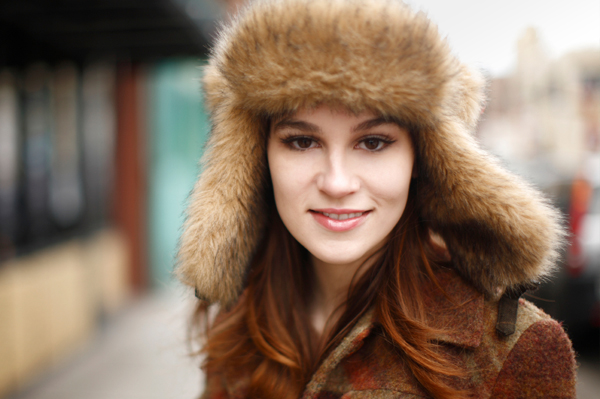 Woman with beautiful skin in a winter trapper hat