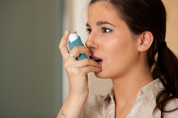 Woman with asthma inhaller
