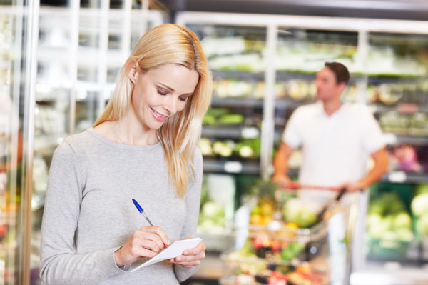 Woman with shopping list in grocery store