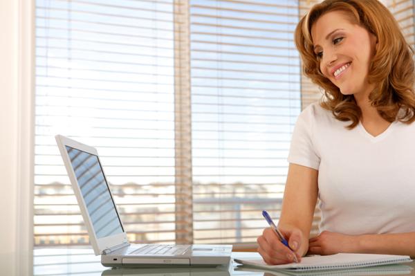 Woman writing notes at home