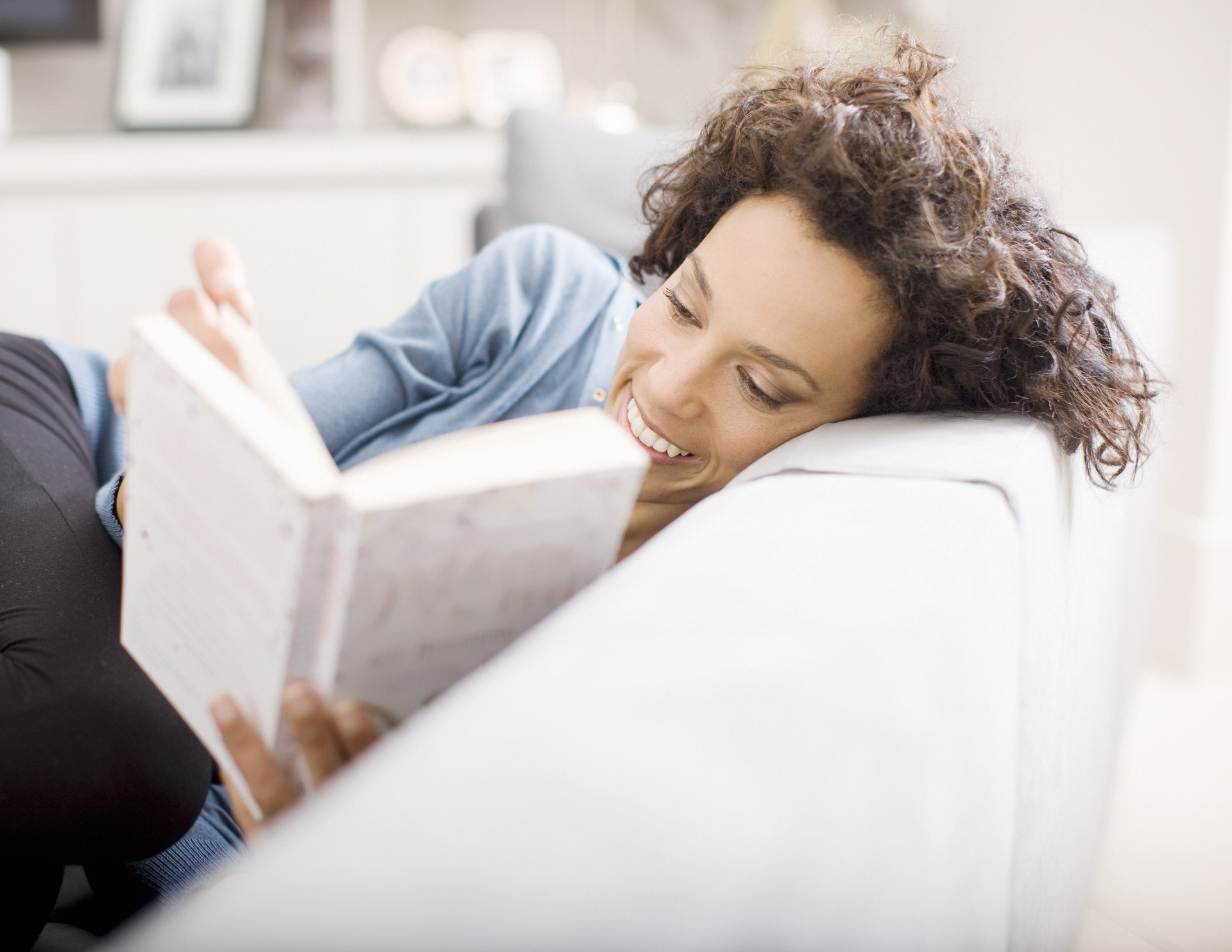 Woman reading book on couch