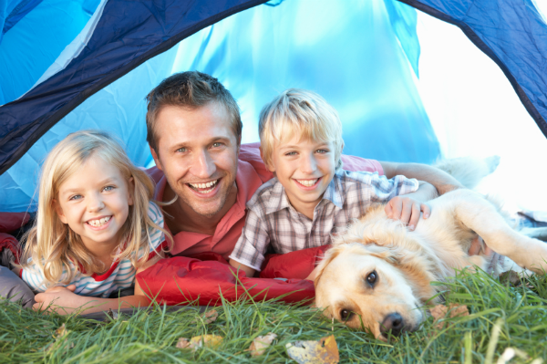 young family camping with their dog