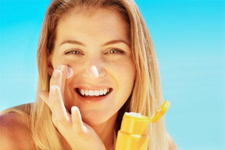 Young woman applying sunblock