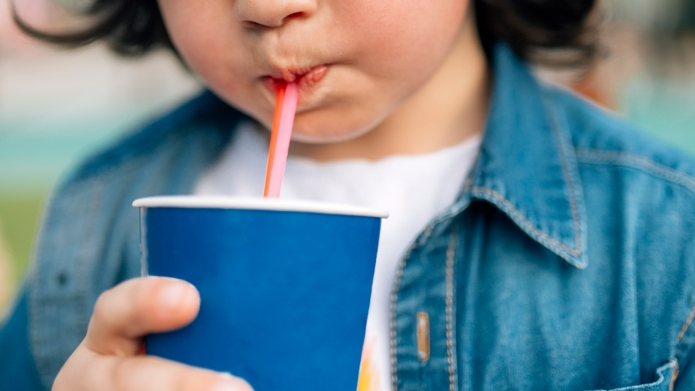 Boy drinking with straw from disposable