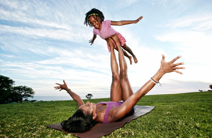Mother balancing daughter on legs in