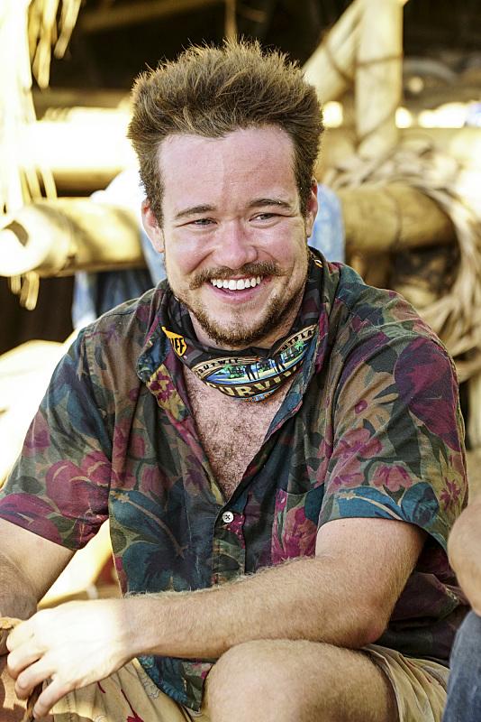 Zeke Smith smiles at camp on Survivor: Millennials Vs. Gen-X