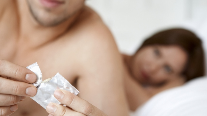 Man Opening Condom With Woman In