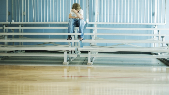 Teenage boy sitting alone on bleachers