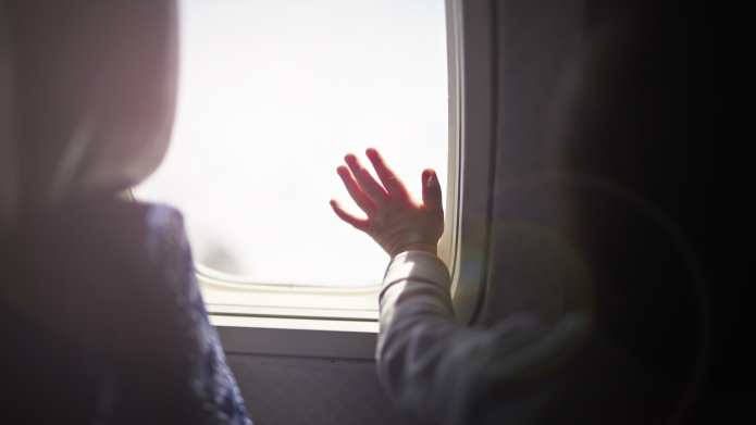 Young child looking out airplane window