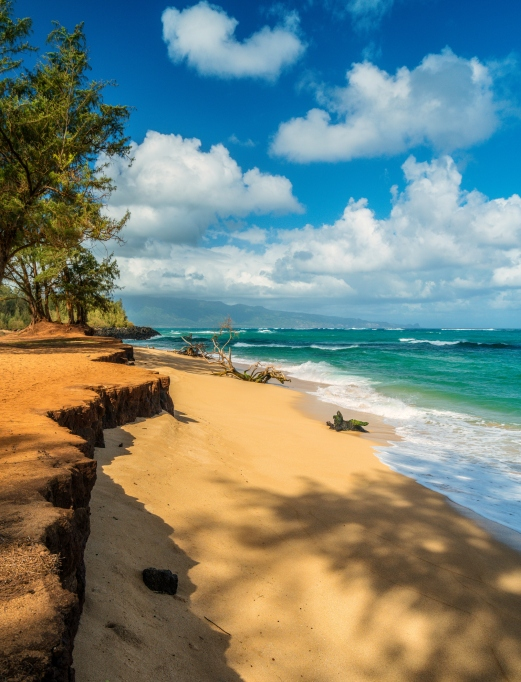 Ocean surf washing up on the smooth warm sand of Paia Bay Beach. Located on the North Shore of Maui, Hawaii. USA.