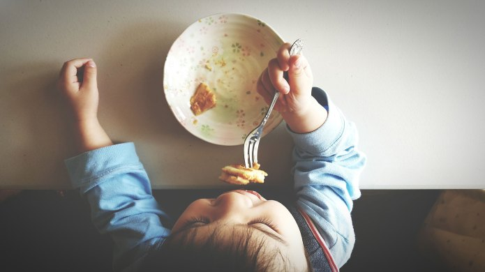 Boy eating food from above.