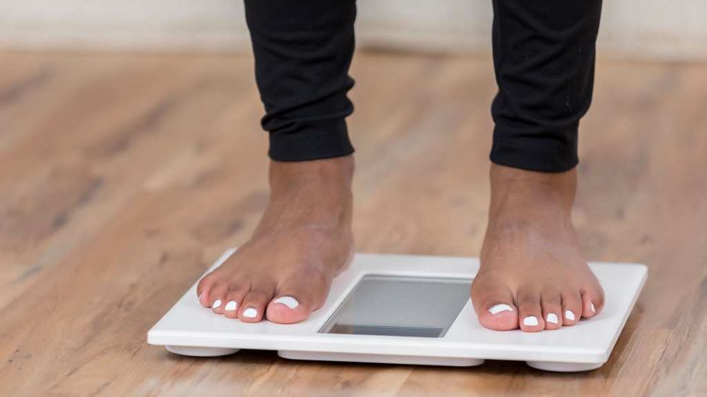 A pair of female feet with painted toes can be seen standing on a white bathroom scale. The scale sits on a wooden floor and there is copy space.
