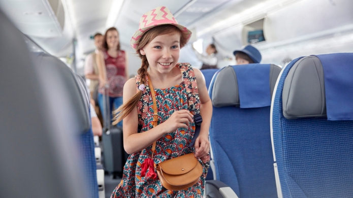 Smiling, eager girl boarding airplane