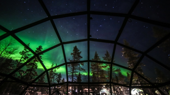 Aurora borealis, also known as Northern lights shining in the night sky seen from Glass Igloos, Kakslauttanen Arctic Resort West Village, Saariselkä, Lapland, Finland.