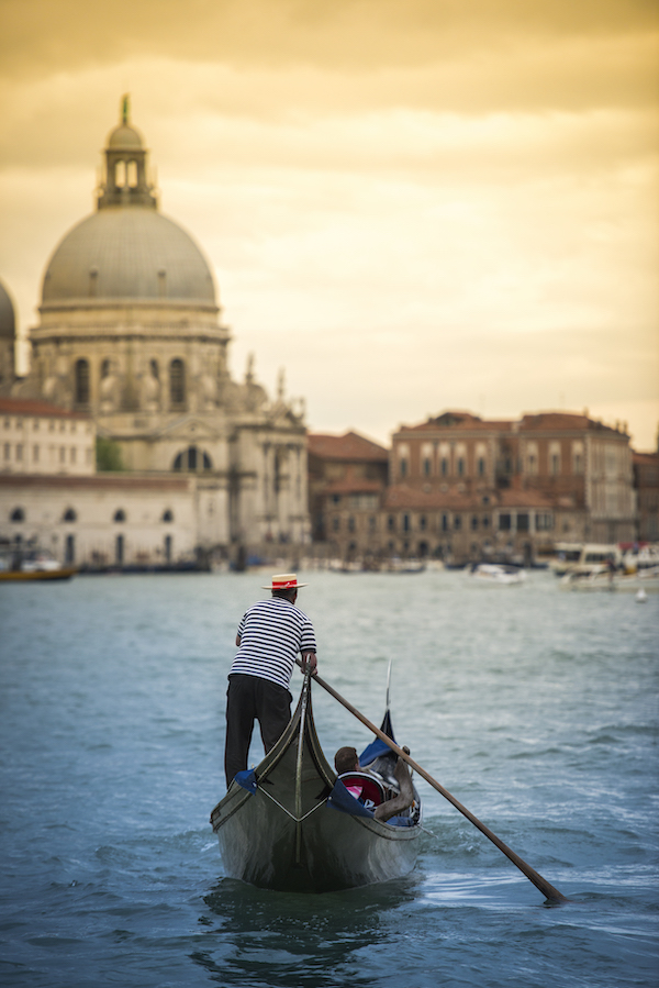 A gondola slowly makes its way toward a large church on the Grand Canal in Venice, Italy.