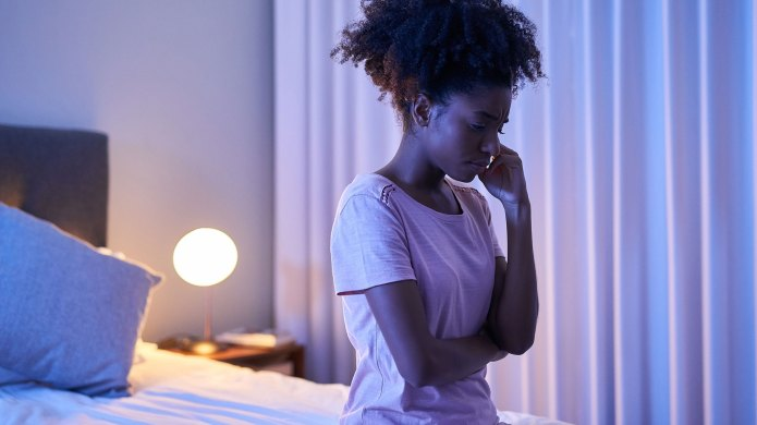 Woman sitting on bed with insomnia