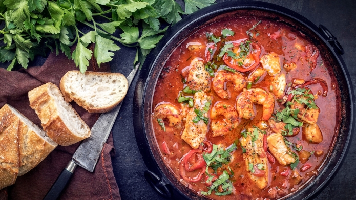 Traditional Creole cajun court bouillon with fish and seafood gumbo chowder stew as top view in a pot ; Shutterstock ID 1069575905