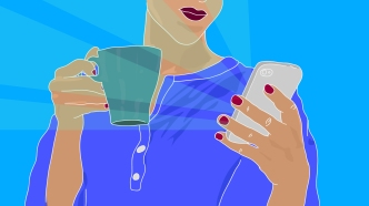Woman holding mug and checking phone