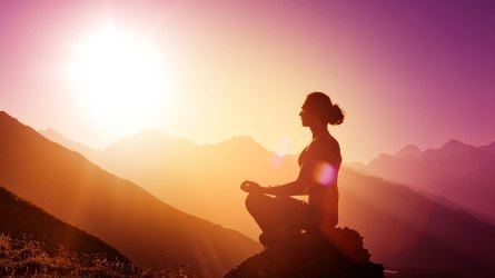 Woman meditating on a mountain during
