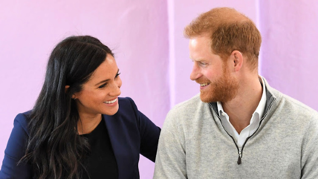 Meghan Markle and Prince Harry chat in front of a pink wall