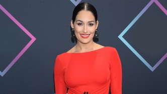 Nikki Bella alone in red dress.