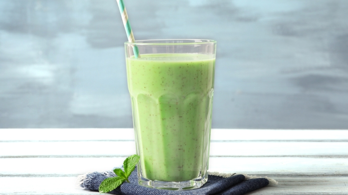 Glass with green milkshake on table;