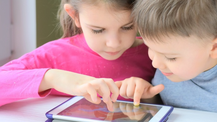 Two children play on a tablet