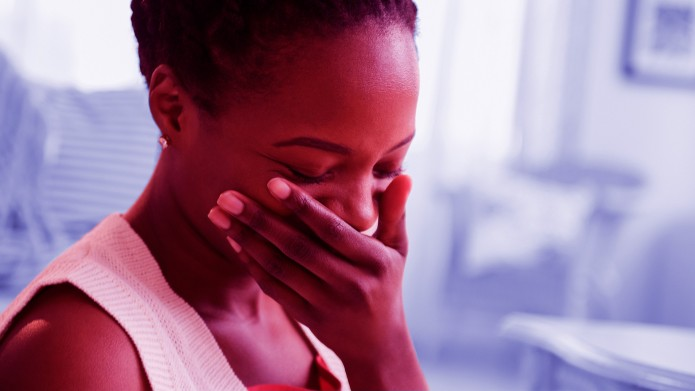 Amused or embarassed Black woman laughing