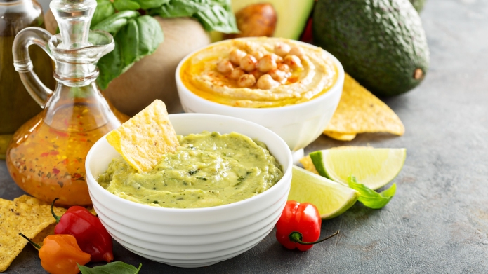 Guacamole and hummus in white bowls