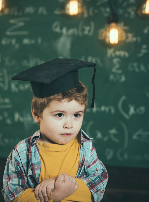 Smart child in graduate cap on serious face, shy, holds hands crossed. Kid, preschooler or first former, chalkboard on background, defocused. Graduate concept. Boy looks cute in square academic cap.; Shutterstock ID 1059781286; Purchase Order: n/a