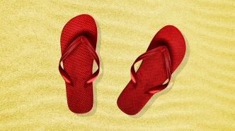 Red flip flops in the sand.