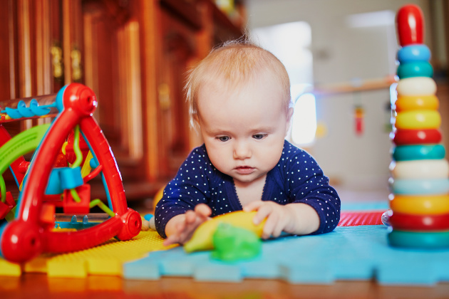 Baby plays with toys during tummy time