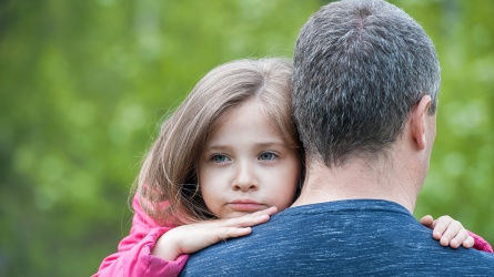 Dad holds daughter, who peers over