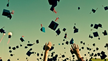 Students throw graduation caps in the