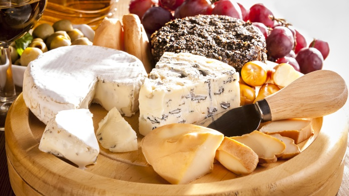 Various cheeses on the board and