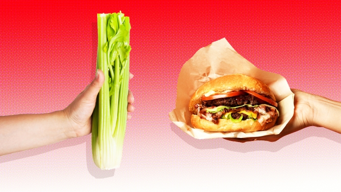 Celery and cheeseburger on red background
