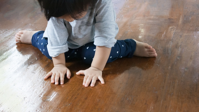 child sitting on wood floor