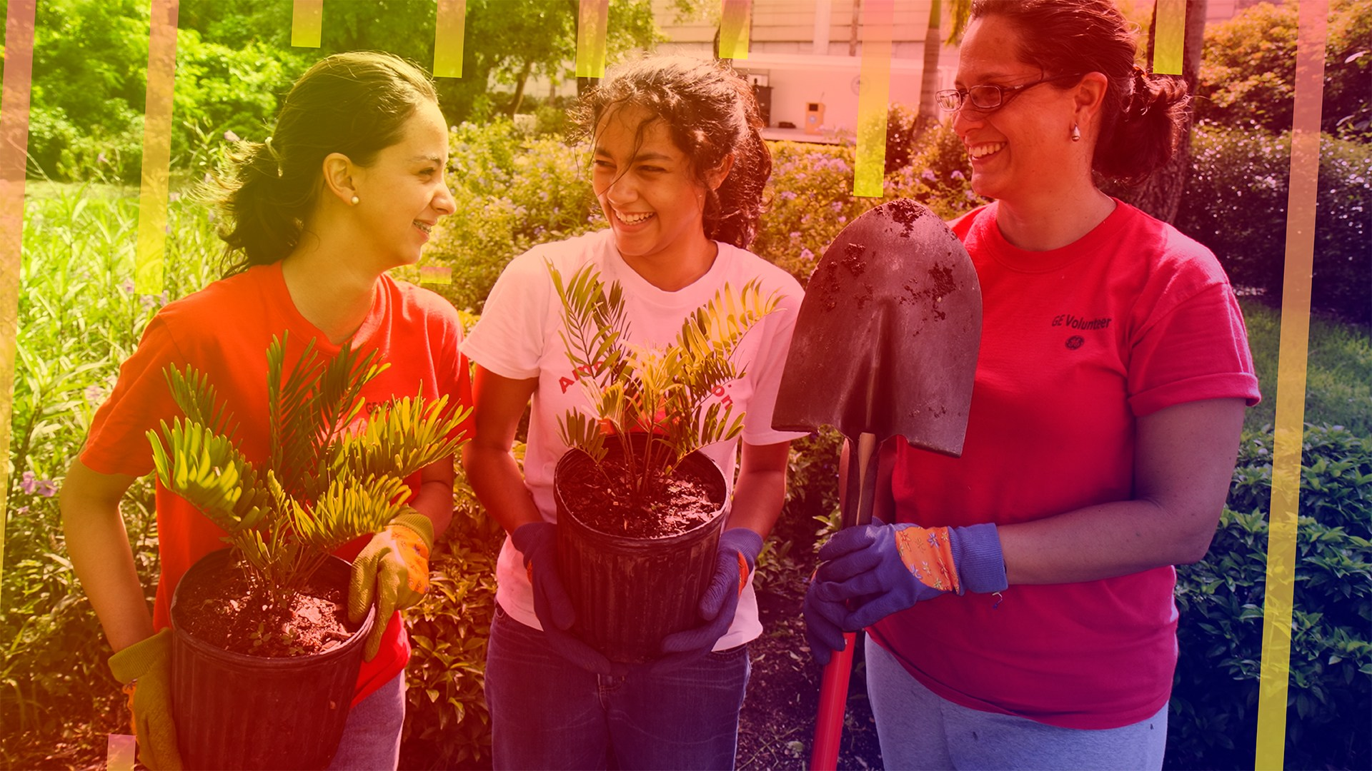 daughters and mother help plant a garden