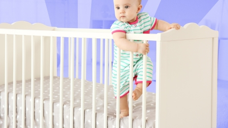 crib sheets: baby standing in crib