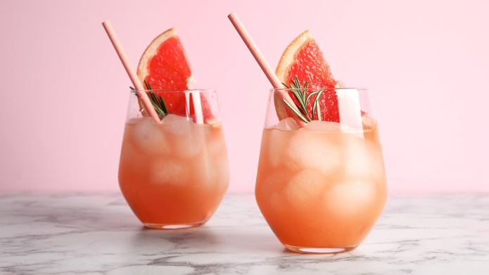 Glasses of grapefruit cocktail on table