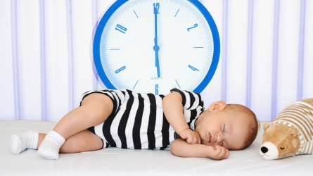 Baby sleeping next to clock