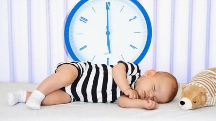 Baby sleeping next to clock