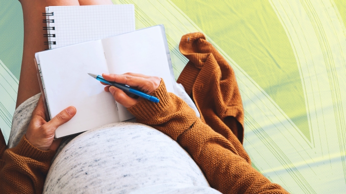 Pregnant woman writing in notebook