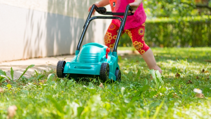 child pushing toy lawn mower